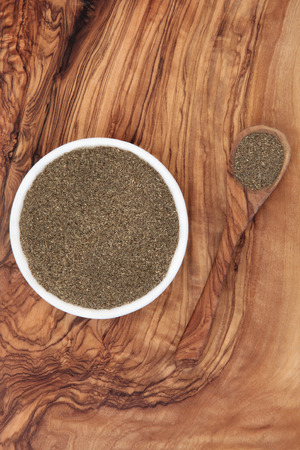 greying: Bhringaraj kesharat herb powder ayurvedic alternative medicine over olive wood background. Eclipta alba. Used as a liver tonic and hair loss remedy and for premature greying.