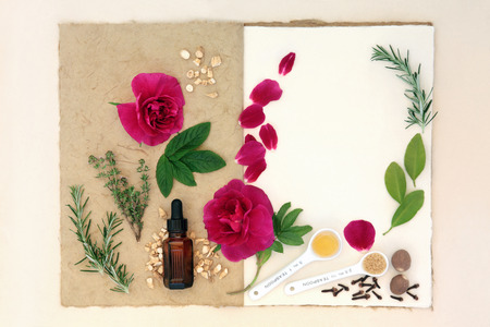 essentials: Love potion ingredients over natural hemp notebook and mottled cream paper background.