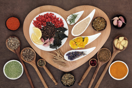 metabolism: Superfood immune boosting selection in white porcelain dishes and wooden bowls over heart shaped board and lokta paper background.