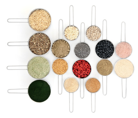 Body building powders and health food in metal scoops over white background. photo