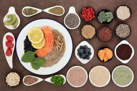 Large health food selection in bowls over lokta paper background. photo