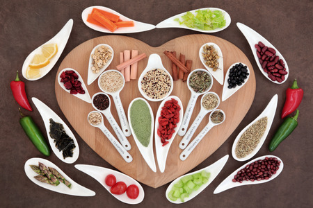 Large weight loss and diet super food selection in porcelain bowls and measuring spoons over brown paper background. photo