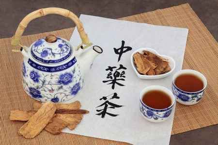 Astragalus herb tea also used in chinese herbal medicine, with cups and calligraphy script on rice paper over bamboo. Translation reads as chinese herbal tea. photo