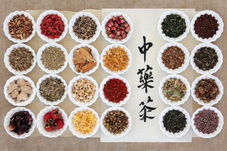 Herb tea selection also used in herbal medicine in porcelain bowls over brown paper background with chinese calligraphy script on rice paper.
