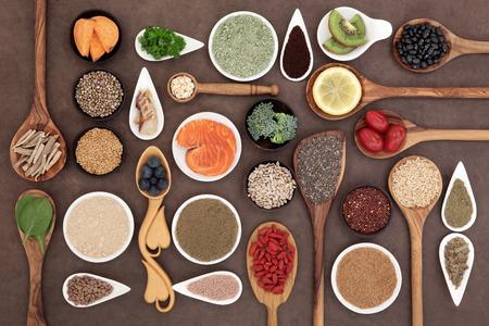 SALUD: Edificio del cuerpo y la selección de alimentos saludables súper con suplemento en polvo en tazones y cucharas sobre fondo de papel lokta. Foto de archivo