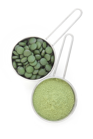 wheat grass: Chlorella tablets and wheat grass powder in metal scoops over white background. Stock Photo