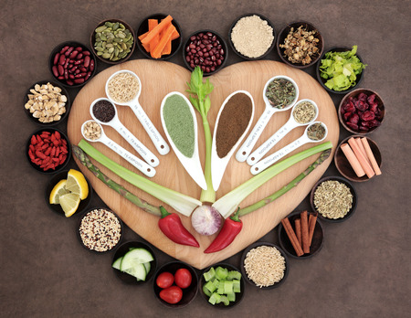sampler: Large healthy heart superfood selection in wooden bowls and measuring spoons over brown paper background.