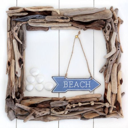 Driftwood frame and beach sign with cockle shells over wooden white background. photo