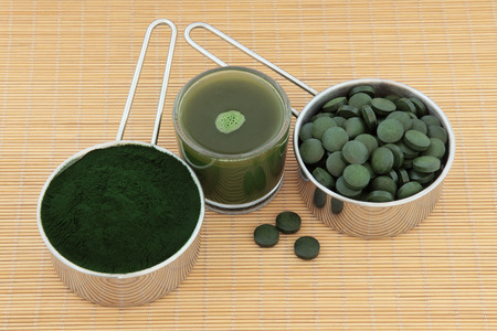 muscle building: Chlorella tablets, spirulina powder and drink over bamboo background .