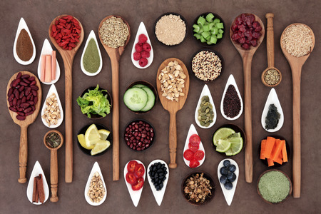 Large diet and weight loss superfood selection in bowls and spoons over lokta paper background. Archivio Fotografico