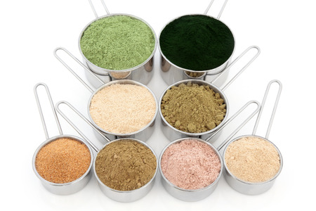 superfood: Body building and health food supplement powders over white background. Wheatgrass, spirulina, macca root, hemp, pomegranate, ginkgo biloba, chocolate whey, ginseng. Top to bottom, left to right