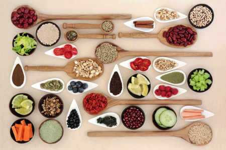 Large diet and weight loss superfood selection in bowls and wooden spoons over mottled cream background.