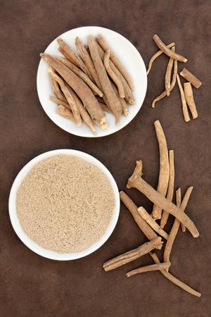 Ginseng ashwagandha herb root and powder over handmade lokta paper background. Zdjęcie Seryjne - 33780172