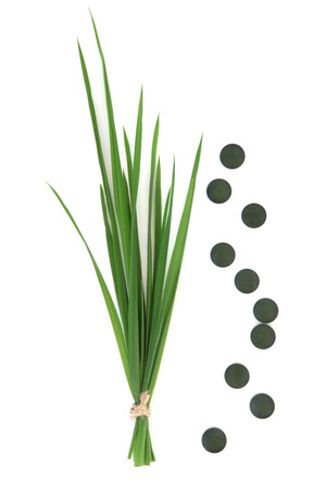 Chlorella tablets and wheat grass over white background. Archivio Fotografico