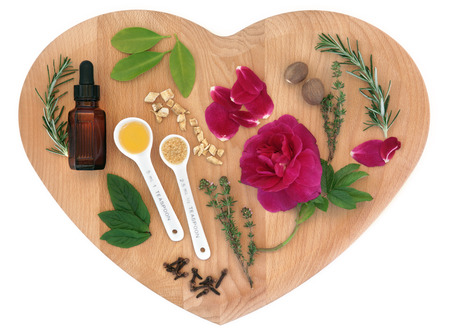 wicca: Love potion ingredients on a heart shaped wooden board over white background.
