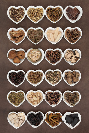 Large chinese herbal medicine selection in heart shaped porcelain bowls over lokta paper background. photo