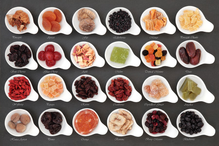 Large dried fruit selection in white bowls over slate background with titles.