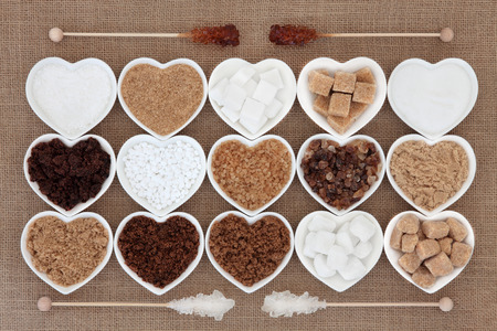 sugar: White and brown sugar selection in heart shaped bowls with crystal lollipop sticks over hessian background.