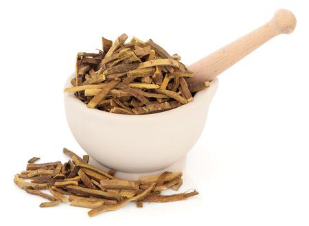 白い背景上杵と石臼でアムール コルク木樹皮ハーブ。黄の黄砂。中国の漢方薬で使用されている 50 の基本的なハーブの一つ。 写真素材