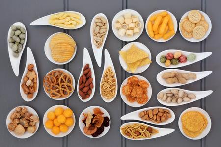 comida chatarra: Amplia selecci�n de aperitivos salados en platos de porcelana sobre fondo de madera gris.