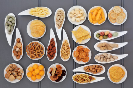 party food: Large savoury snack selection in porcelain dishes over grey wooden background. Stock Photo