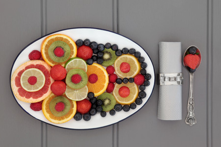 napkin ring: Fresh fruit diet food selection in a white dish with silver spoon, napkin and ring over wooden grey background.
