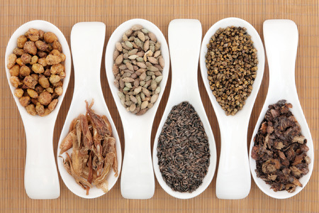 Chinese herbal medicine selection in porcelain spoons over bamboo.