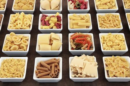 legumbres secas: Pasta seca selección de alimentos en blanco cuadrados platos de porcelana sobre fondo de papel lokta .. Foto de archivo
