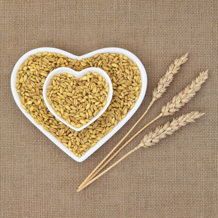 Kamut khorasan wheat in heart shaped dishes over hessian background with ears of wheat.