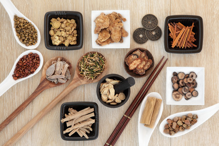 Chinese herbal medicine selection with I ching coins, mortar with pestle and chopsticks over light oak background. Zdjęcie Seryjne - 35834374