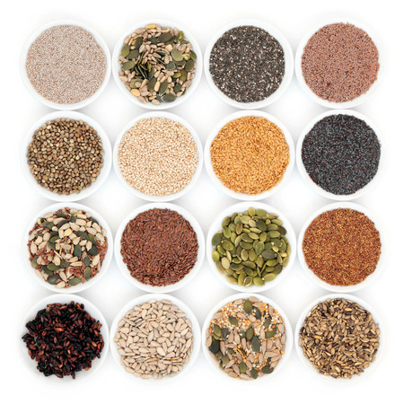 Seed and nut health food in porcelain bowls over white background. Banque d'images