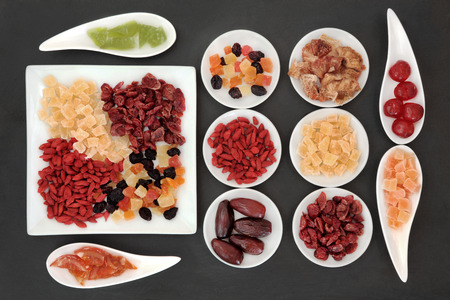 Healthy dried fruit selection in white porcelain bowls over slate background. photo