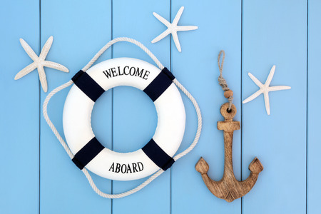 Decorative lifebuoy, anchor and starfish sea shells over wooden blue background. Stockfoto