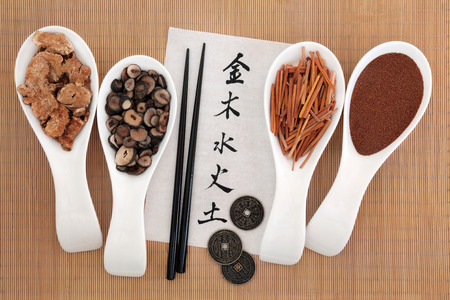 five element: Five elements chinese calligraphy script on rice paper with herbal medicine selection. Metal, wood, water, fire, earth characters, top to bottom. Stock Photo