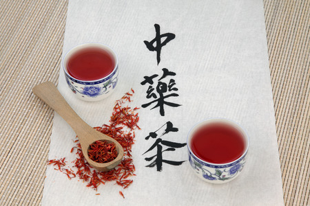rice paper: Safflower herb tea also used in chinese herbal medicine, with cups, wooden spoon and calligraphy script on rice paper. Translation reads as chinese herbal tea.