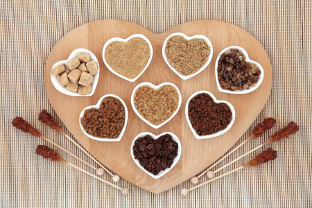 unhealthy diet: Brown sugar with crystal lollipops in abstract design on a wooden heart shaped board over bamboo background.