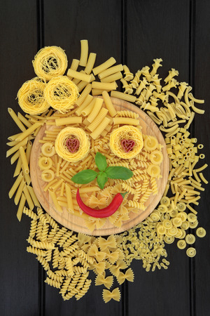 smiley: Pasta selection with abstract smiley face on a wooden board over dark wood background.. Stock Photo