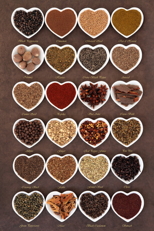piri: Large spice selection in heart shaped dishes over lokta paper background with titles.