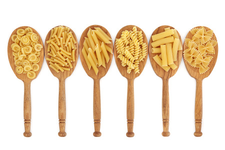 Pasta food selection in oak wood spoons over white background. photo