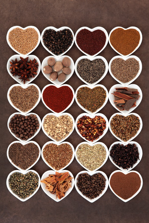 piri piri: Large spice collection in heart shaped porcelain dishes over lokta paper background. Stock Photo