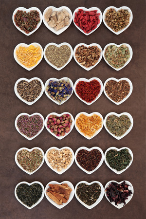 teas: Large herb tea selection in heart shaped porcelain bowls over lokta paper background.