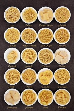 Large pasta dried food selection in round bowls over brown lokta paper background with titles.