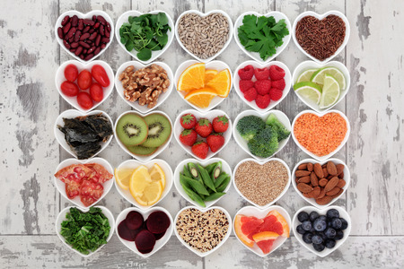 food dish: Diet detox super food selection in heart shaped porcelain bowls over distressed wooden background.