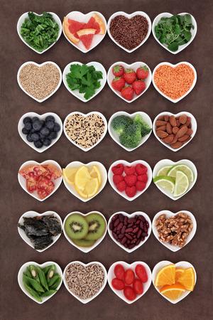 Large selection of diet detox super food in heart shaped porcelain bowls.