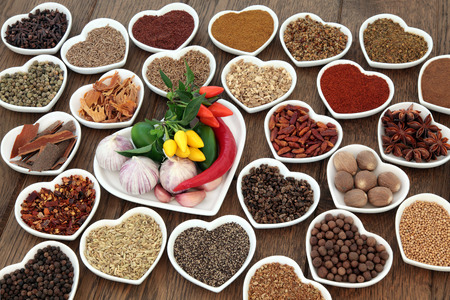 piri: Herb and spice ingredients in heart shaped porcelain dishes over old oak background. Stock Photo