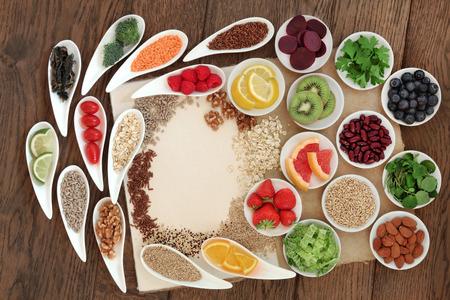 Diet detox super food selection in porcelain bowls on a speckled hemp paper notebook over oak wood background.