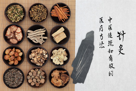 traditional: Chinese herbal medicine with acupuncture needles and calligraphy script. Translation describes acupuncture chinese medicine as a traditional and effective medical solution. Stock Photo