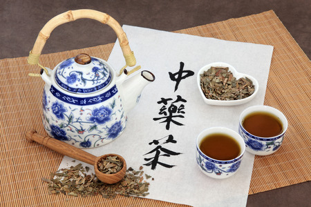 teapot: Ginkgo herb tea also used in chinese herbal medicine, with teapot, cup and calligraphy script on rice paper over bamboo. Translation reads as chinese herbal tea.
