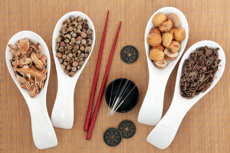 Acupuncture needles and chinese herbal medicine selection with chopsticks and I ching coins over bamboo background.