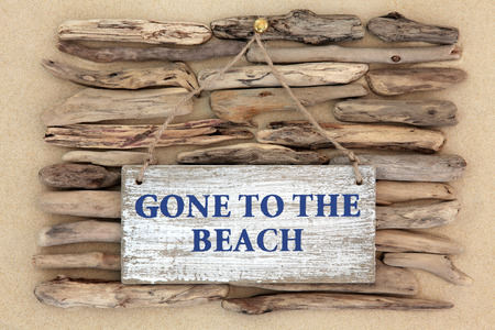driftwood: Gone to the beach weathered sign on driftwood and sand background.